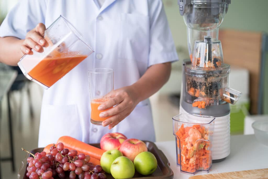 Woman juicing cold pressed juice and pouring into bottle.Wellness food or detox smoothie.Vegetable and fruit juice healthy with food juicer machine.