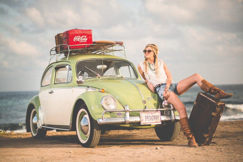 海岸でかわいい車と女性。